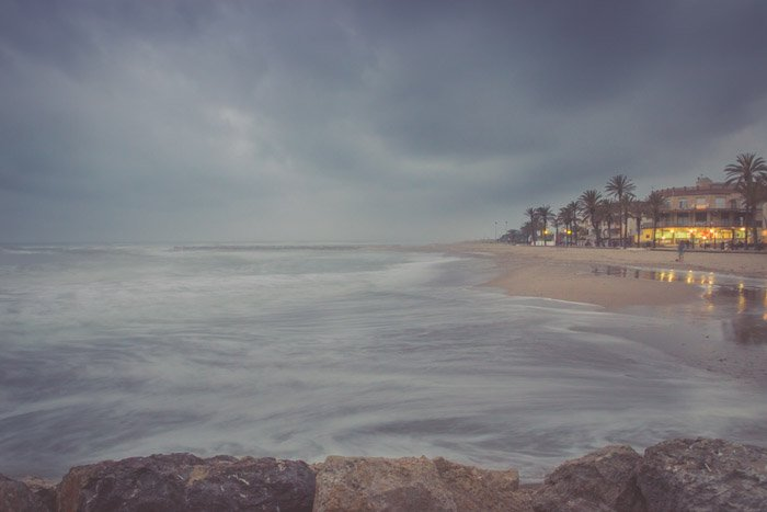 A coastal seascape photographed during a storm with a beach house to the right of the frame