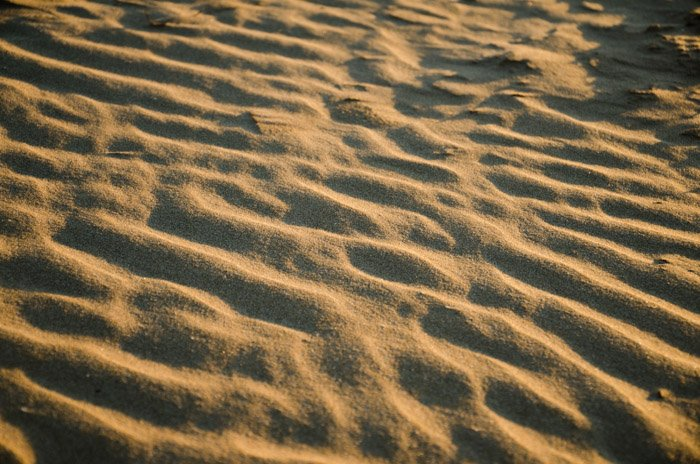 A close up photo of textured sand