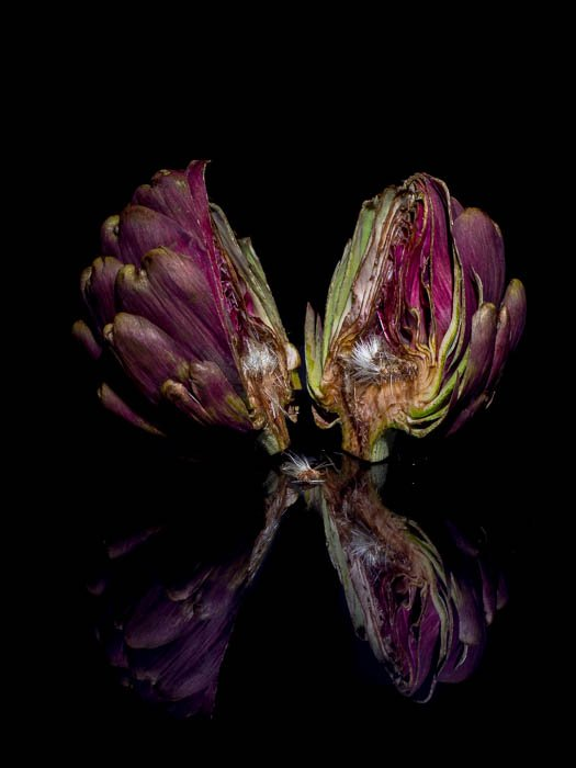 An artichoke cut in half in front of a black background with its reflection