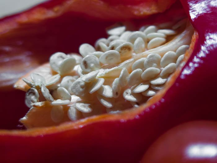 A red bell pepper cut, seeds showing