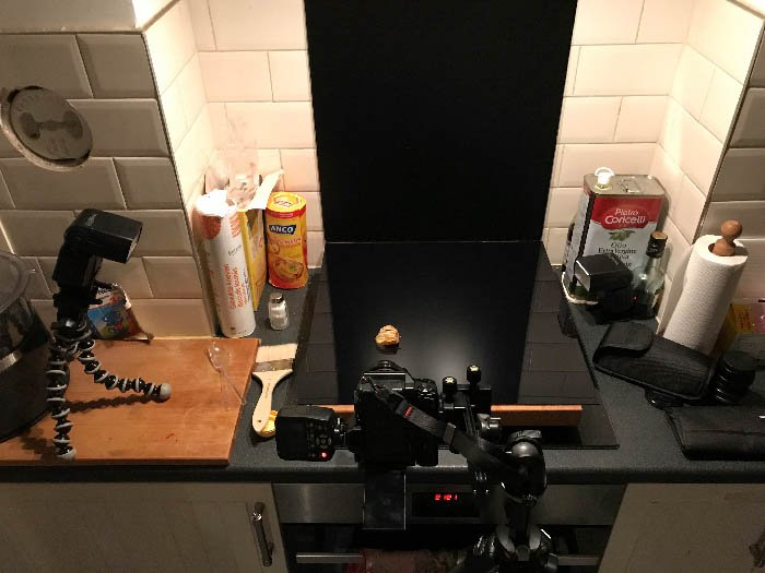 Makeshift studio in the kitchen with a camera and a flash