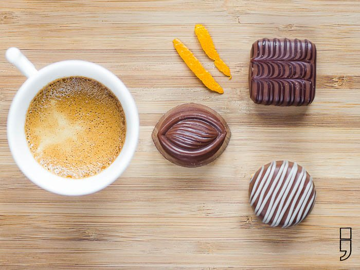 A cup of coffee with pralines on a wooden plate