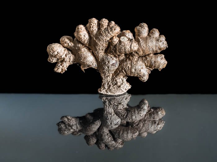 A ginger root in front of a black background with its reflection