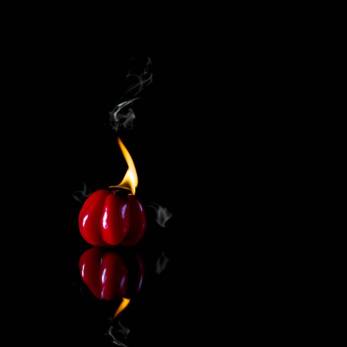 Creative food photo of a red pepper thats so hot it's on fire