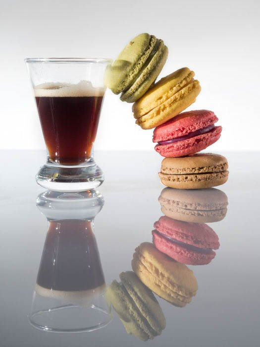 A stack of rainbow macarons beside a coffee cup