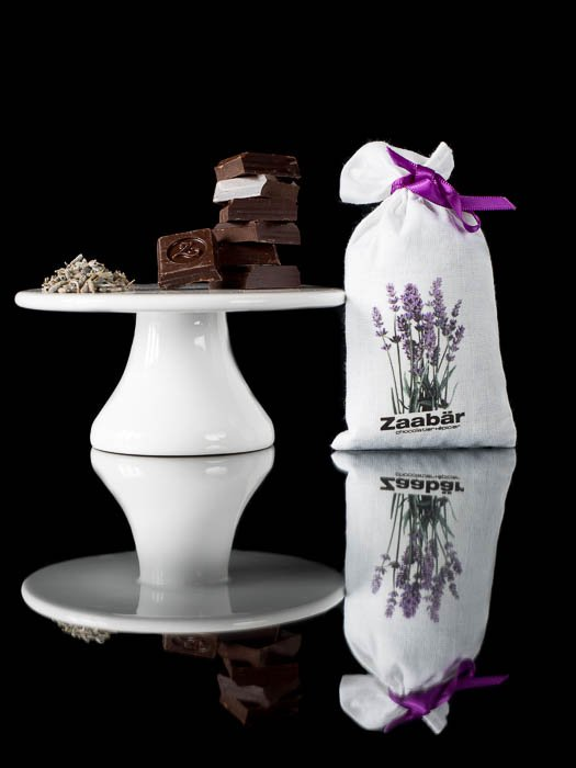 Squares of chocolate on a cake stand with a lavender bag next to it