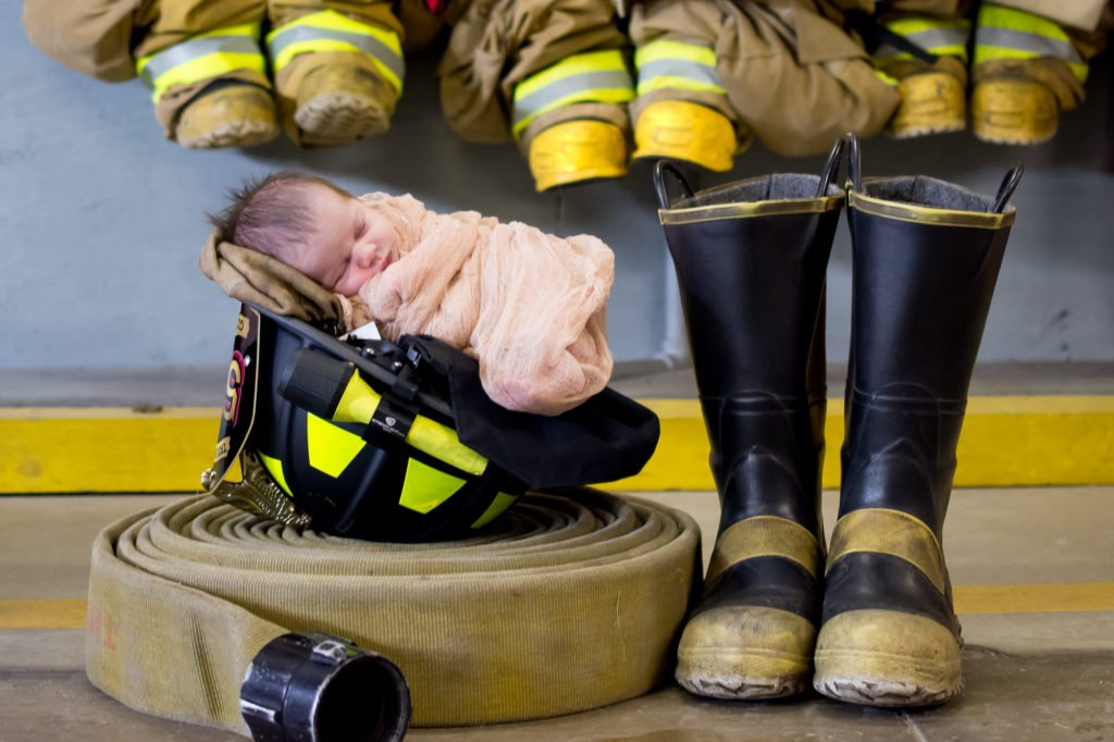 newborn baby in pink blanket photographed sleeping in a fireman's helmet, by fireman's hose and boots