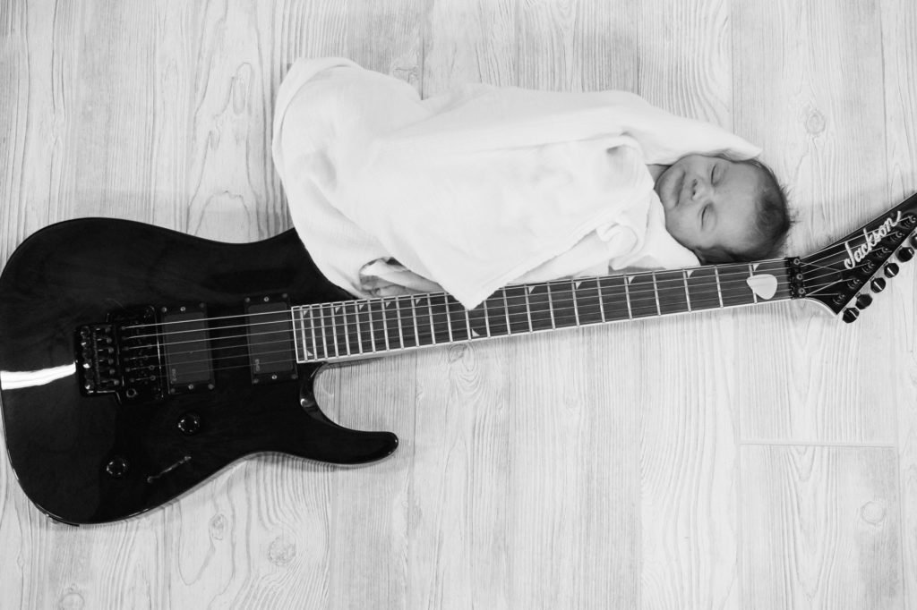 black and white photo of newborn baby wrapped in a white blanket beside a black guitar, shot from above. newborn photography