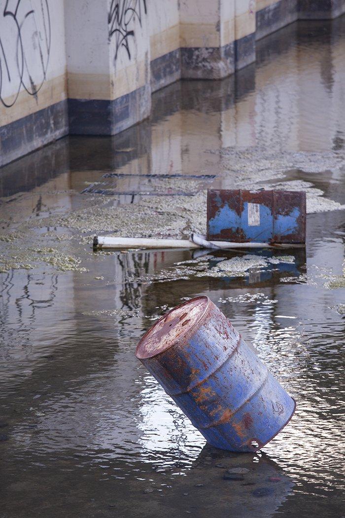 rusty blue waste barrels floating in a river