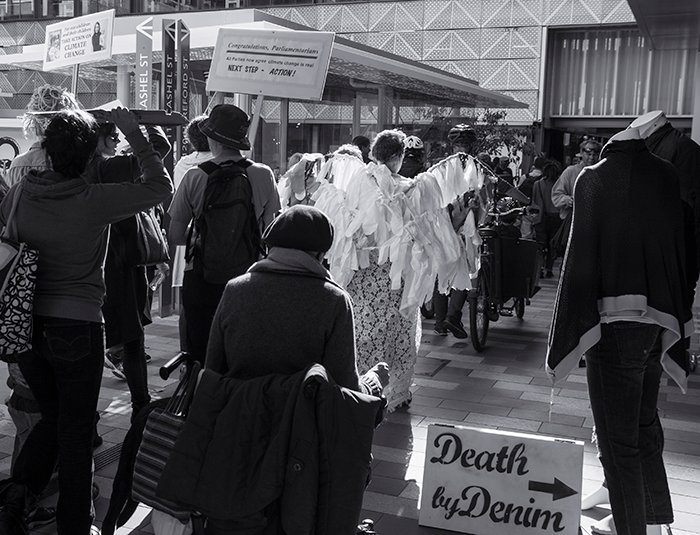 black and white photograph of a group of protesters in front of buildings and shops