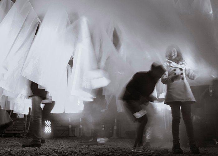 movement and blur in documentary photography - black and white photograph using slow shutter speed of people moving between white material