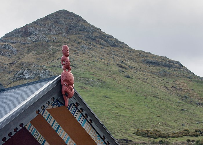 red aboriginal carving sculpture on a rooftop in front of a mountain