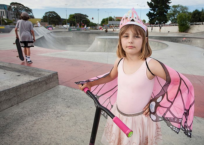 little girl in pink princess butterfly costume with a scooter, skate park in the background