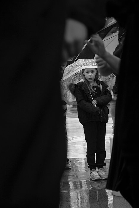 black and white documentary photography of a little girl holding an umbrella framed by larger figures