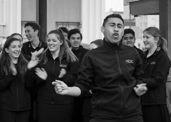 black and white documentary photography of a group of people singing and clapping