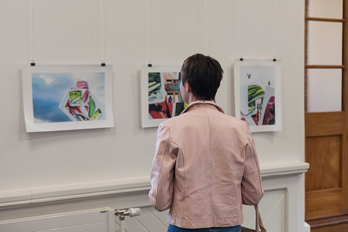 woman in pink jacket looking at paintings in an art exhibition