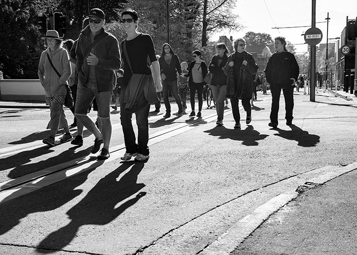black and white photograph of a crowd of people walking by