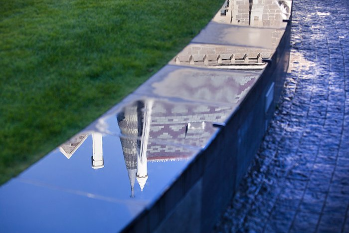 reflected image of Christchurch arts centre on a wet wall
