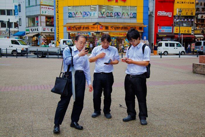 three men looking at their phones on the street