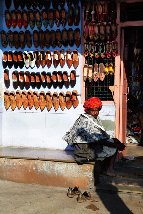 a street vendor sitting by hisi stall