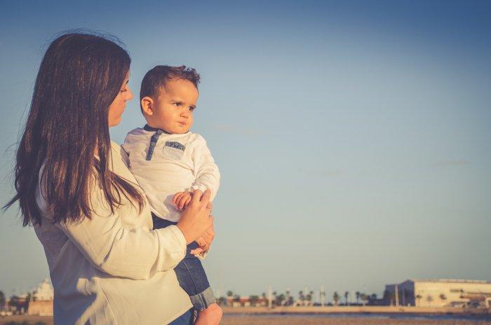 A mother holding a little boy outdoors