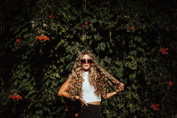 A fashion model posing in front of a bush