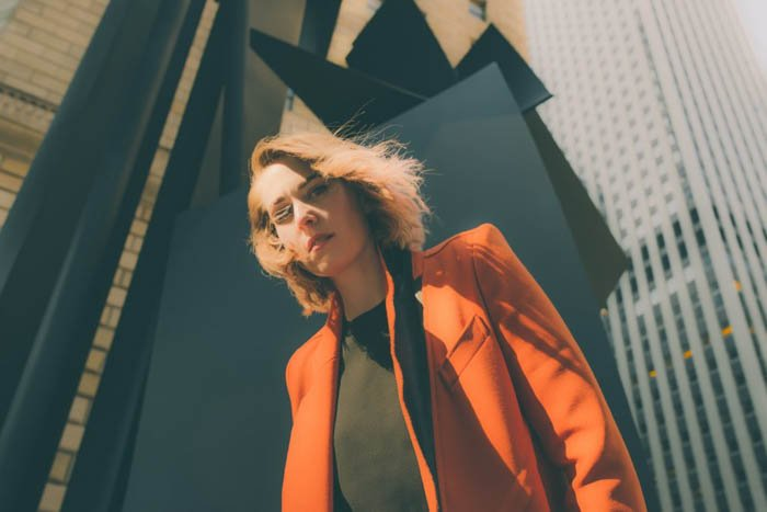 A female photography model posing outdoors wearing an orange jacket - fashion photography composition