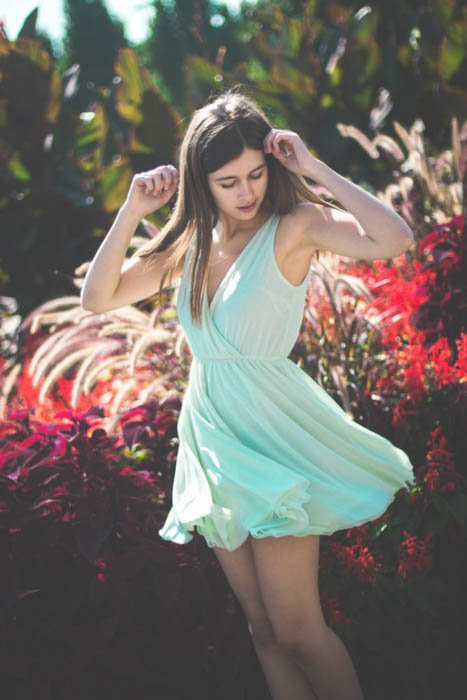 A female photography model posing outdoors wearing flowy light blue summer dress - fashion photography composition