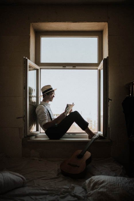 A man sitting in a window frame reading