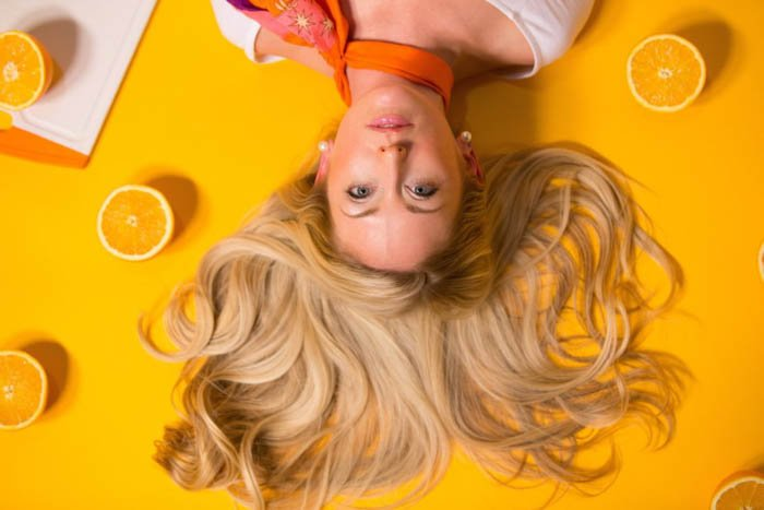 Bright flat lay photo of female photography model posing with lemons on a yellow background - fashion photography composition