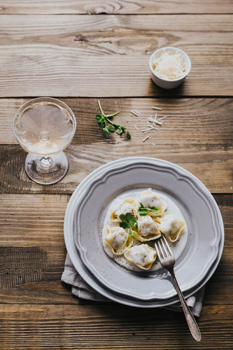 Overhead of fresh tortellini with cream sauce in triangle composition