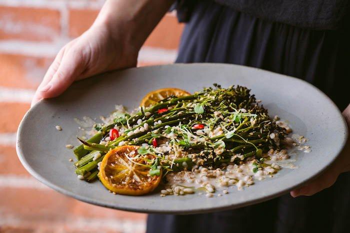 closeup of woman serving broccolini and barley salad