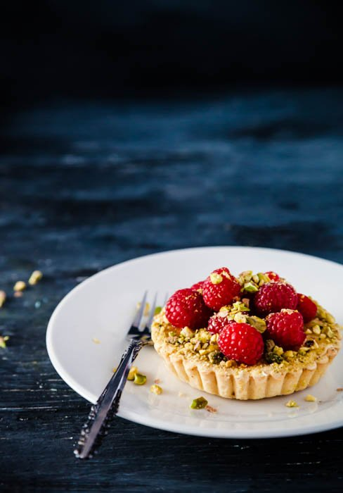 single raspberry pistachio tart with lemon on a white plate with blue background