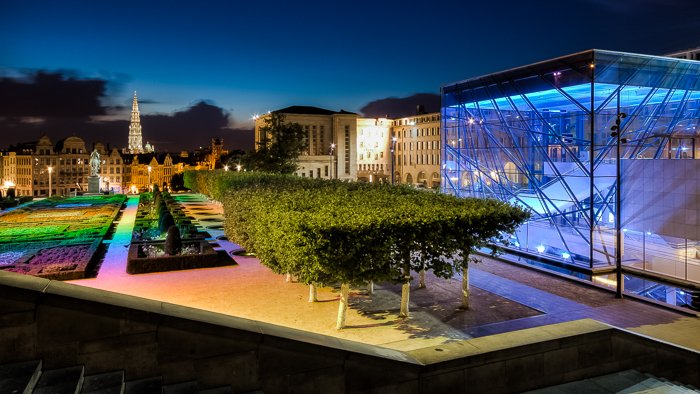 view of the outside of Mons des Arts with bright coloured lights on the garden and buildings