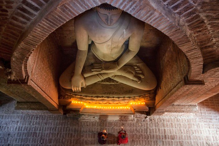 Overhead view of Buddhist monks praying under a statue of Buddha - travel photography accessories