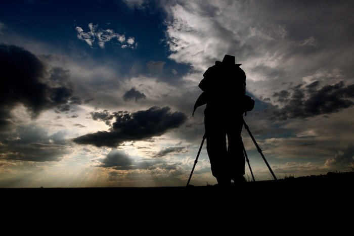 the silhouette of a photographer shooting a landscape on tripod