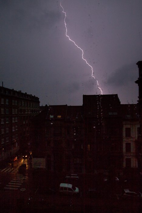 a bolt of lighting striking behind a dark and gloomy Brussels cityscape