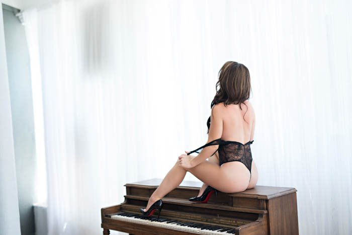 A woman in a sexy pose on a piano