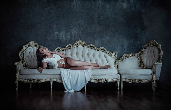 A woman in a sensual pose on a chaise longue