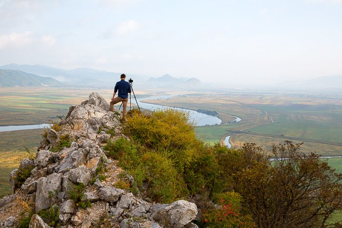 a photographer stands on top a rocky hilltop overlooking a green landscape and river