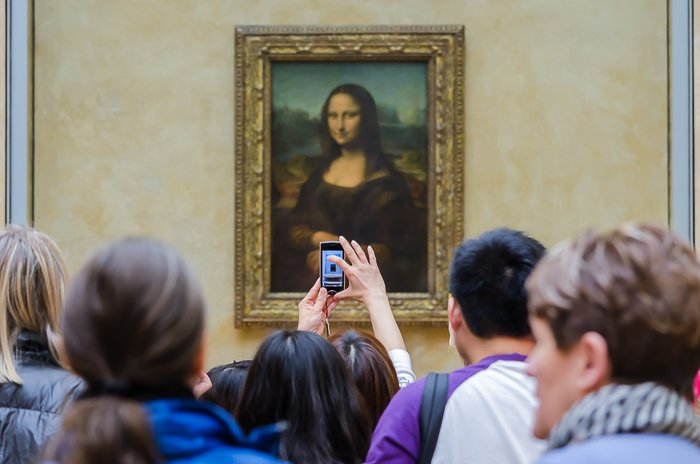 Crowds in front of the Mona Lisa painting while one tourists snaps a picture on her smartphone