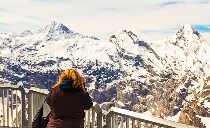 photo of a girl looking from a viewing point at snow capped rocky mountains