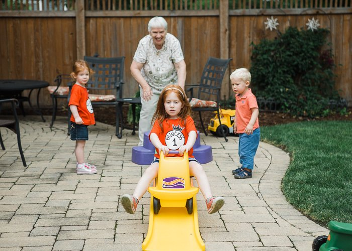 Candid portrait of a grandmother playing outdoors with three young grandchildren