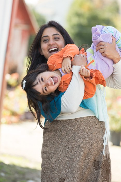 Outdoor portrait of a mother holding her daughter playfully upside down, both smiling towards the camera