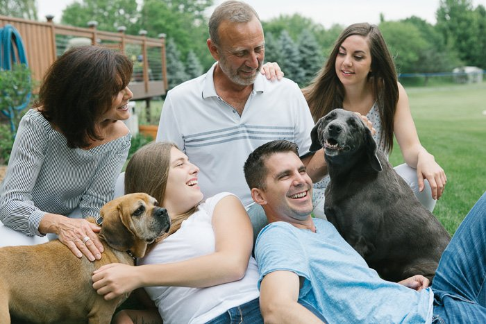 Natural lifestyle shoot of a family lying on the grass with their two dogs