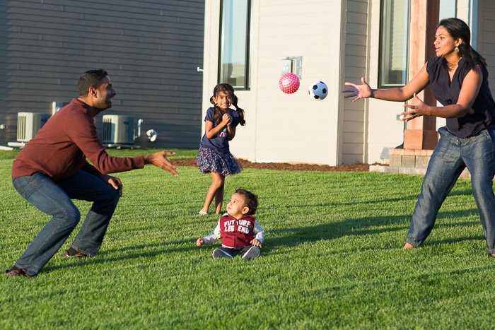 candid portrait of a father and mother playing catch with two young children in the garden
