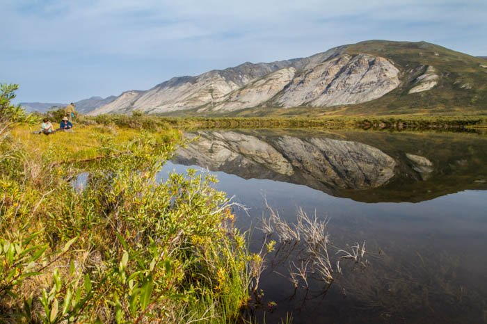 photographing beside a lake in Gates of the Arctic National Park, Alaska on a very bright day, the reflections on the pond mirroring the mountains.