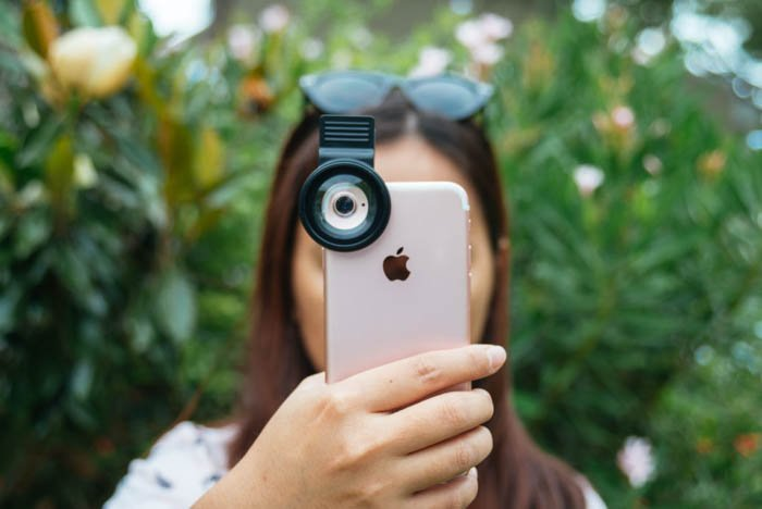 girl taking a photo with an iphone with a clip on macro lens