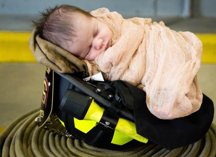 newborn baby in a cute helmet prop