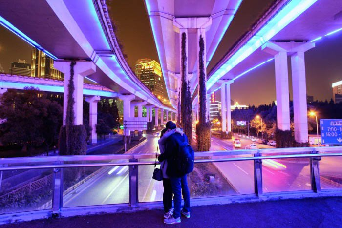 Night photography of a couple embracing under a modern bridge